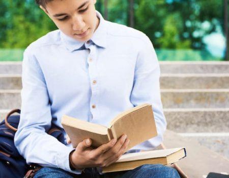 teenage-boy-reading-books-outdoors-UJXP7XP